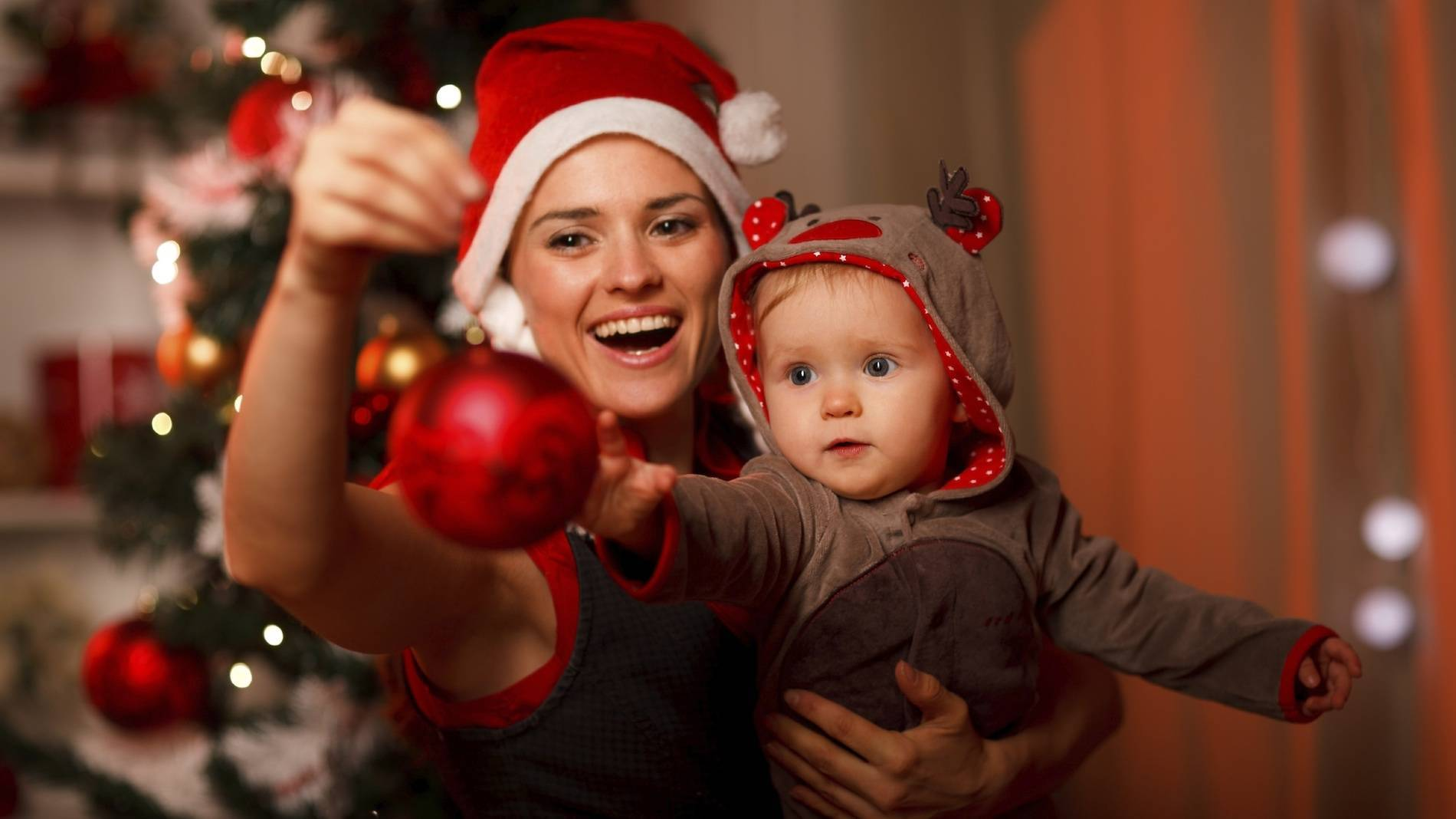 Happy Mother Showing Christmas Ball To Baby Near Christmas